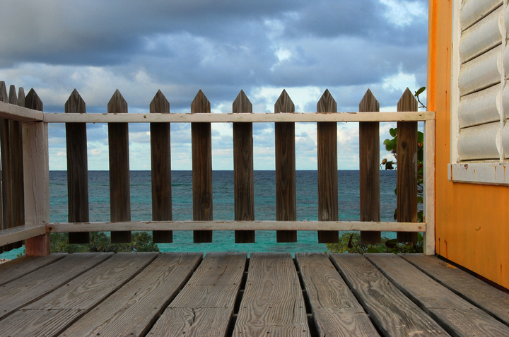 It's not usual to see the sea through a picket fence.  This is a cozy cottage next door to us in Anegada which used to be part of the best campground in the BVI.  Alas, Mac (the owner, who made creating and improving this place the passion of his later life) died a few years ago.  It is no longer operating.  This little porch still stands as a reminder of the simple life at the shore. 	We sure miss you, Mac.    — RM —